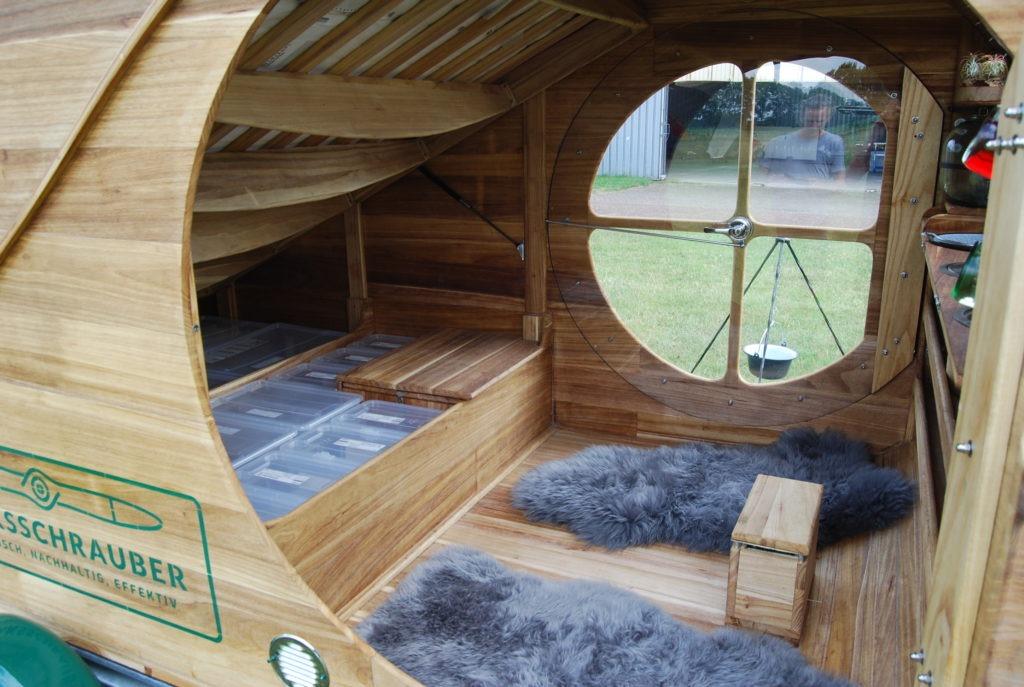 Hochgeklapptes Bett im Camper mit Blick auf den Stauraum